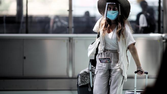Una pasajera caminando con maleta por un pasillo de la terminar T4 del Aeropuerto Adolfo Suárez Madrid Barajas.