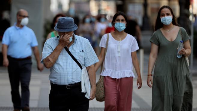 Varios ciudadanos con mascarilla pasean por una calle del centro de Madrid