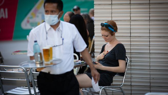 Un camarero sirve en la terraza de un bar de Barcelona.