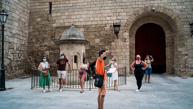 Varios turistas junto al Palacio de la Almudaina de Palma de Mallorca.