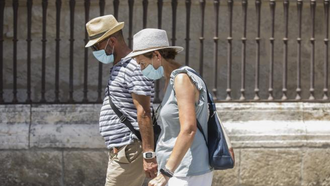 Dos personas pasean con mascarilla y sombrero en Sevilla.