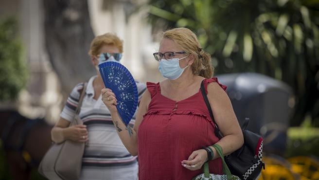 Una mujer con mascarilla se abanica en Sevilla.