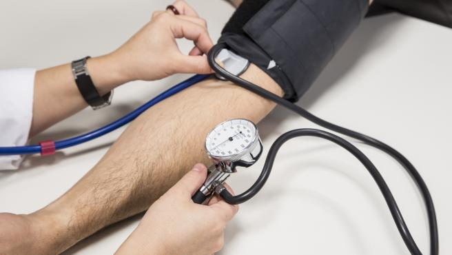 Imagen de archivo de un sanitario utilizando un tensiómetro con un paciente.