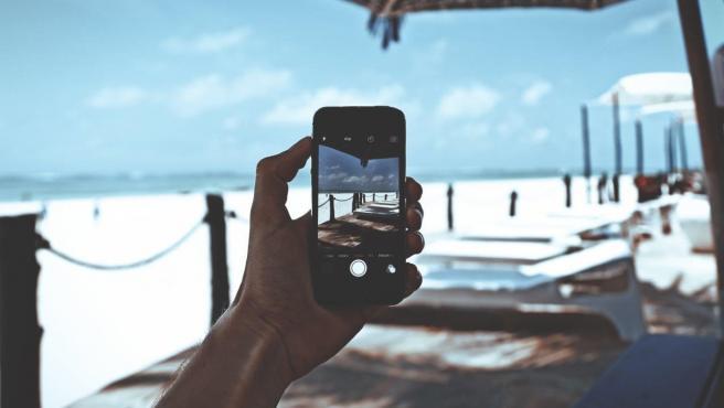 Una persona utiliza un teléfono móvil en la playa.