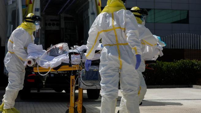 Varios sanitarios trasladan a un paciente desde el interior de la unidad móvil del SUMMA hasta la entrada del Hospital Puerta de Hierro con equipos de protección individual (EPI).