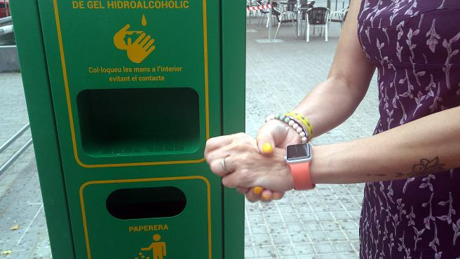 Una persona se aplica gel desinfectante con uno de los dispensadores que el Ayuntamiento de Sabadell ha instalado en la vía pública.