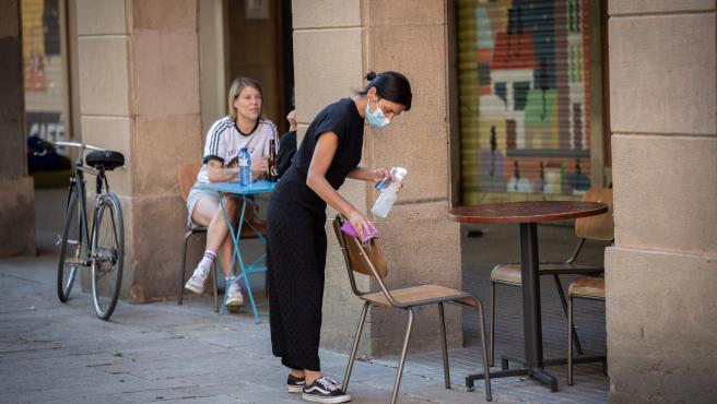 Una camarera limpia varias sillas y una mesa de la terraza de un bar en Barcelona