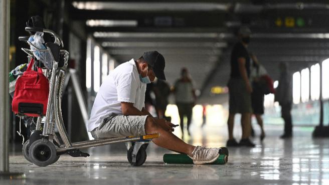 Un viajero espera sentado en el suelo de un pasillo del aeropuerto de Madrid-Barajas.
