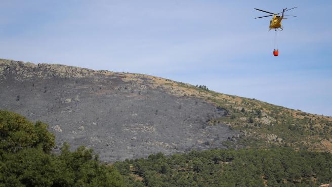Un helicóptero transporta agua para vertirla sobre el incendio forestal originado en el término municipal de Robledo de Chavela (Madrid)