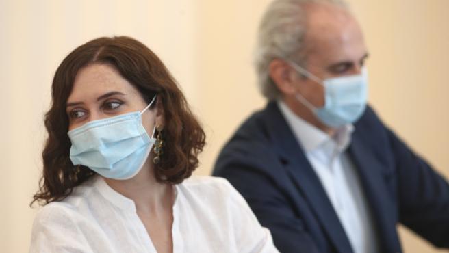 La presidenta de la Comunidad de Madrid, Isabel Díaz Ayuso; y el consejero de Sanidad, Enrique Ruiz Escudero, durante una reunión con una representación de médicos internos residentes (MIR).