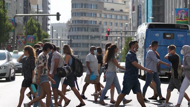 Un grupo de personas con mascarillas cruza un paso de cebra de la Gran Vía de Madrid.
