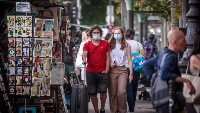 Varias personas pasean por París con mascarilla.