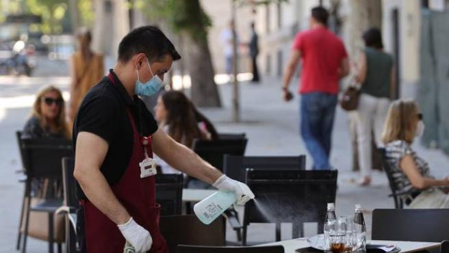 Un camarero desinfecta la mesa de una terraza.