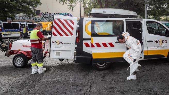 Dos empleados municipales de Sevilla se quitan los trajes de protección tras desinfectar un mercado.