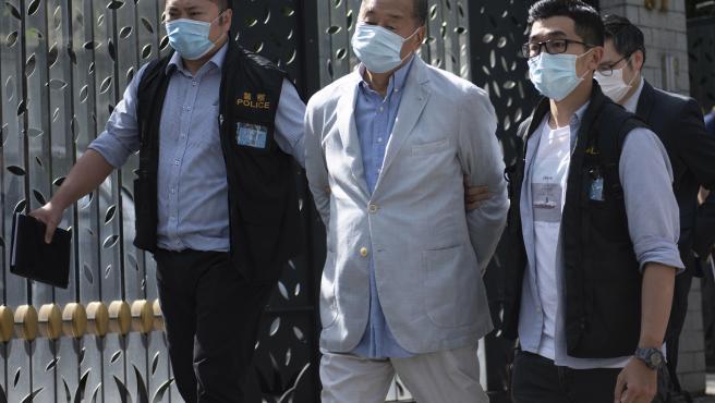 Jimmy Lai (en el centro), el magnate de los medios y fundador de Apple Daily, es detenido en su casa de Hong Kong.