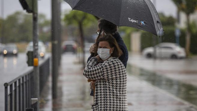 Dos personas sujetan un paraguas durante una tormenta en una imagen tomada durante el estado de alarma