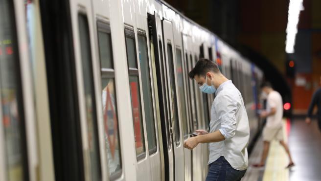 Un pasajero abre la puerta de un tren de Metro de Madrid.