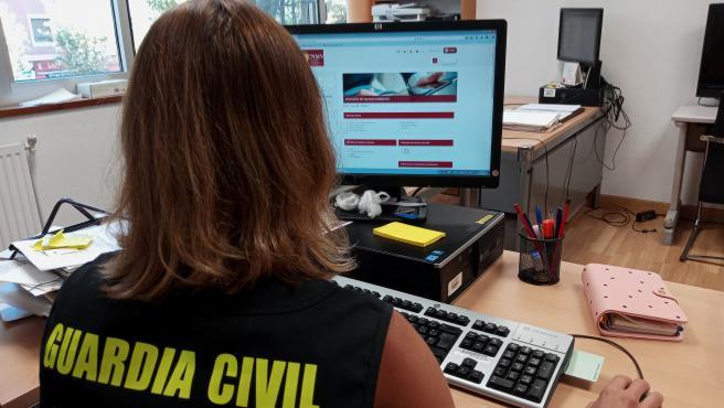 Una agente de la Guardia Civil comprueba la página web de la Comisión Nacional del Mercado de Valores