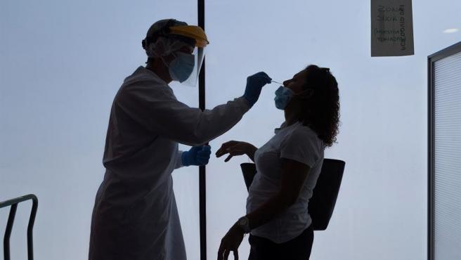 Una sanitaria toma una muestra para hacer una prueba PCR.