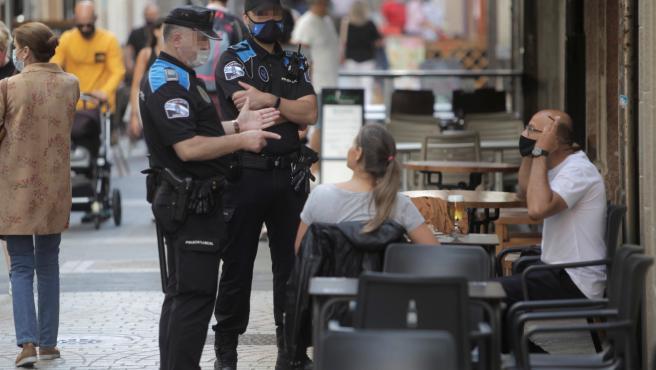 Dos agentes de la policía local de A Coruña se dirigen a un hombre que se encontraba fumando en una terraza de un bar de la ciudad.