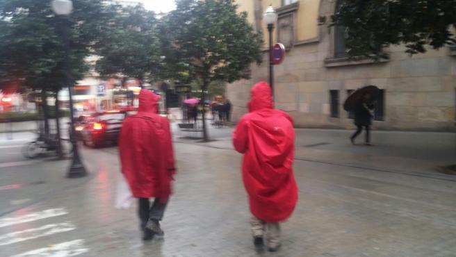Turistas en Gijón, bajo la lluvia