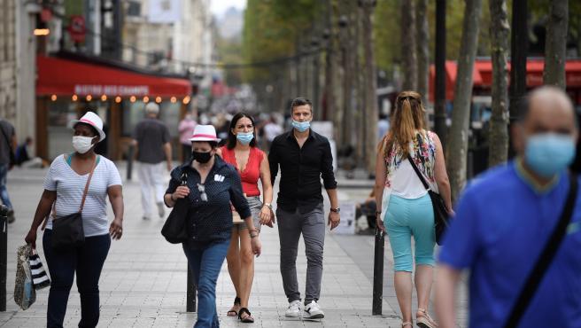 Varias personas paseando por los Campos Elíseos en París.