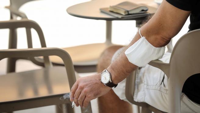 Un hombre fuma un cigarro en una terraza de Valencia.