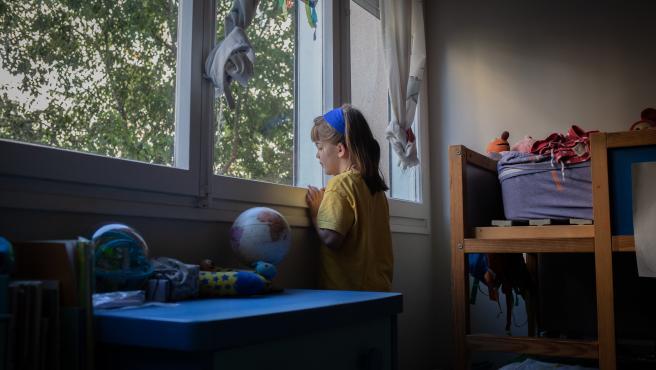 Una niña mira por la ventana en una imagen de archivo.