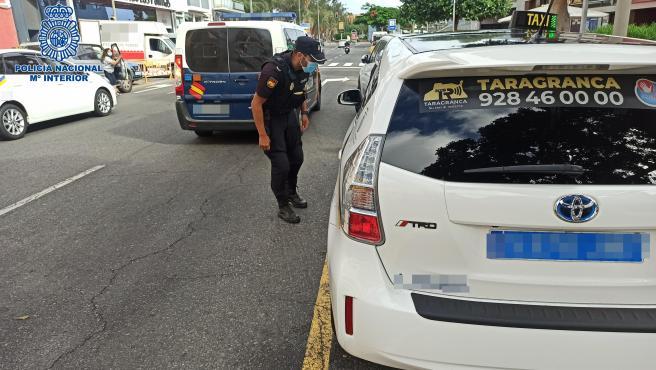 Agente de la Policía Nacional habla con un taxista