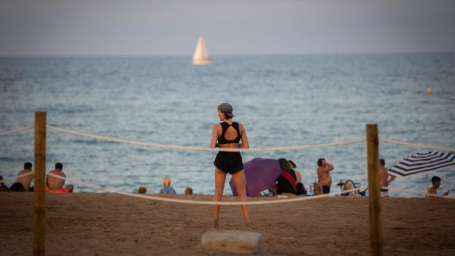 A bañistas, de espaldas a la cámara, en la playa de Barcelona, Cataluña (España), 28 de julio de 2020.