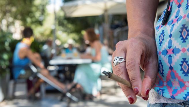 Una persona fuma cerca de una terraza.