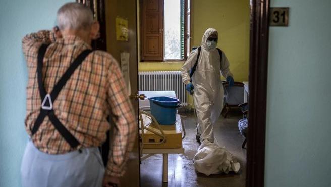Un anciano contempla en una residencia la actuación del personal sanitario.
