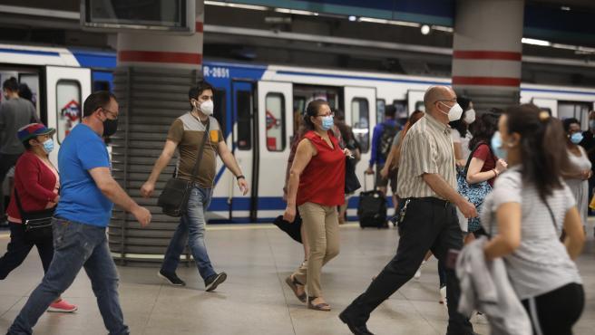 Pasajeros con mascarilla salen de un vagón en la estación de Metro de Atocha, en Madrid (España), a 22 de junio de 2020.
