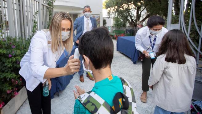 na trabajadora toma la temperatura a un niño a la entrada del colegio privado internacional American School of Barcelona.