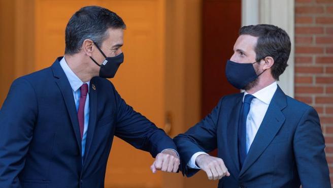 El presidente del Gobierno, Pedro Sánchez, y el líder de la oposición, Pablo Casado, se saludan a la entrada del Palacio de La Moncloa donde se reunieron para analizar los retos para hacer frente a los efectos sociales y económicos de la pandemia.