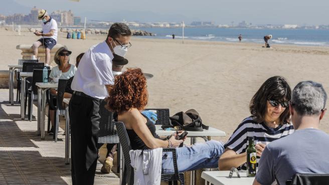 Persones en la terrassa d'un bar al costat de la platja.