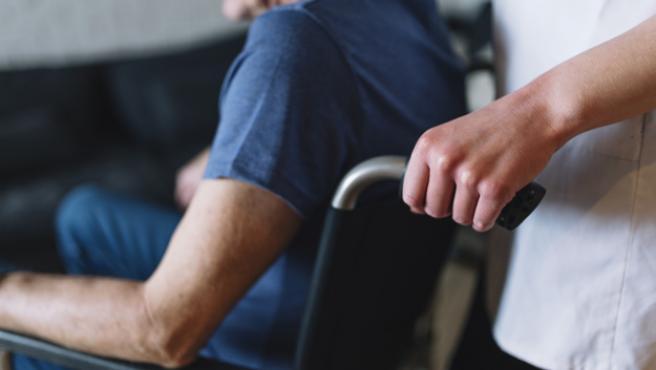 cuidador empujando la silla de ruedas de un anciano