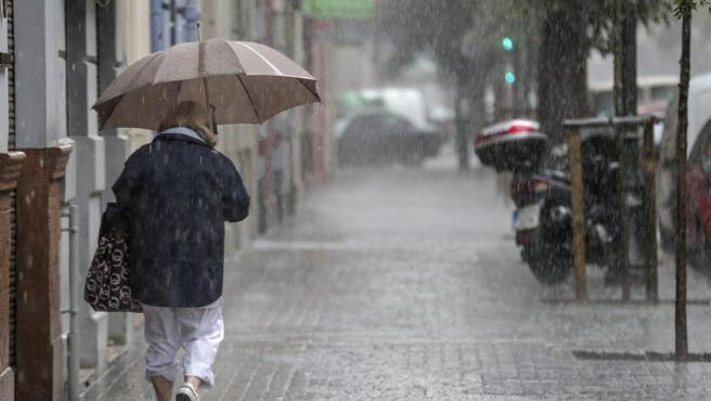 Imagen de una mujer paseando en un día de lluvia.