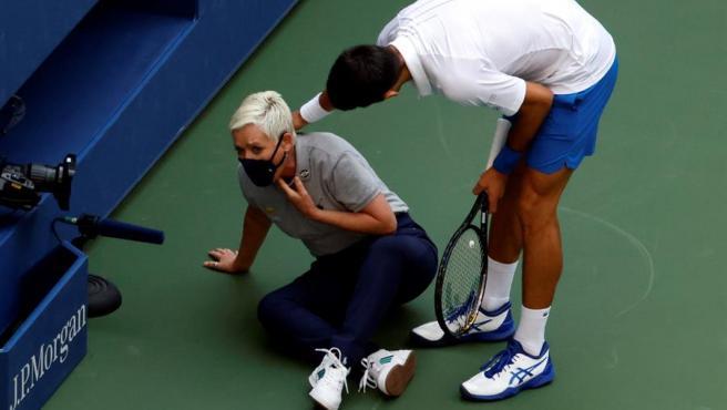 El tenista serbio Novak Djokovic intenta ayudar a una juez de línea tras darle un pelotazo en la garganta durante su partido contra el español Pablo Carreño en el Abierto de EE UU, en Nueva York.