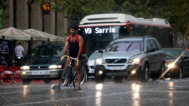 Un ciclista y varios turismos bajo la lluvia en la Avenidad del Paral·lel de Barcelona, en una imagen de archivo.