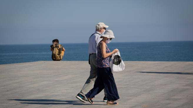 Two people protected with masks walk along the Paseo Marítimo de la Playa de la Barceloneta, in Barcelona / Catalunya (Spain) on May 20, 2020.