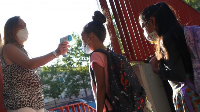 Una trabajadora toma la temperatura a una alumna antes de acceder a un colegio en Madrid, el primer día de la vuelta al cole en los centros públicos y concertados.