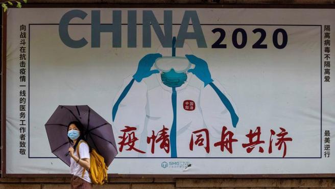 """Una mujer con mascarilla por el coronavirus pasa junto a un cartel en el que puede leerse """"China 2020, luchando juntos contra la pandemia"""", en Shanghái, China."""