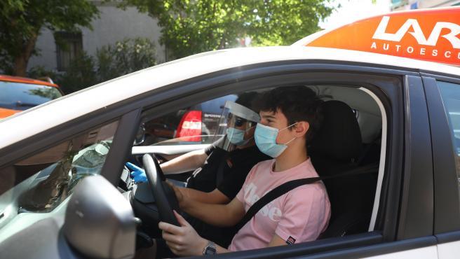 Un profesor de autoescuela, protegido con mascarilla, guantes y pantalla protectora, viaja en coche con un alumno