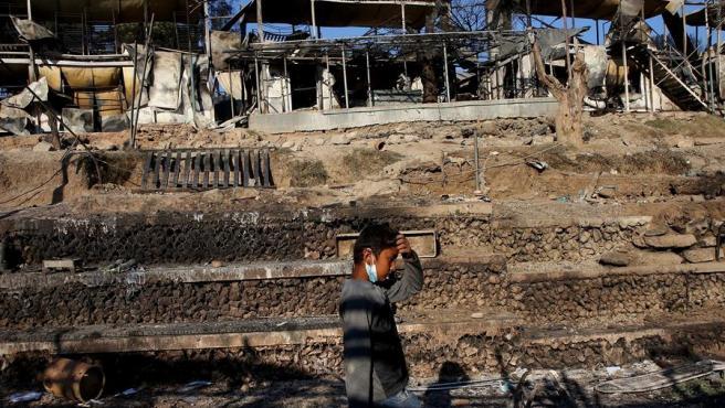 Un niño camina entre las instalaciones destruidas por un incendio en el campo de refugiados de Moria, en la isla de Lesbos (Grecia).