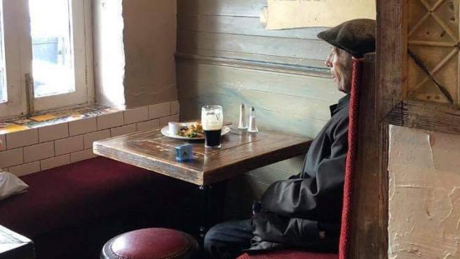 Un hombre se toma su pinta de 'Guiness' mientras cronometra el tiempo que le queda antes de abandonar el local por el límite de tiempo establecido en las medidas para prevenir los contagios de Covid-19, en Irlanda.
