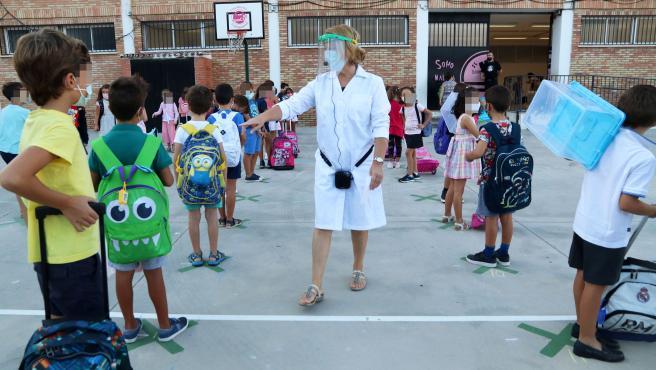 Una profesora indica a los niño cómo entrar al centro en Málaga