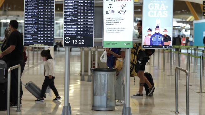 Pasajeros cerca de páneles informativos en la terminal T4 del aeropuerto Adolfo Suárez Madrid-Barajas, en Madrid.