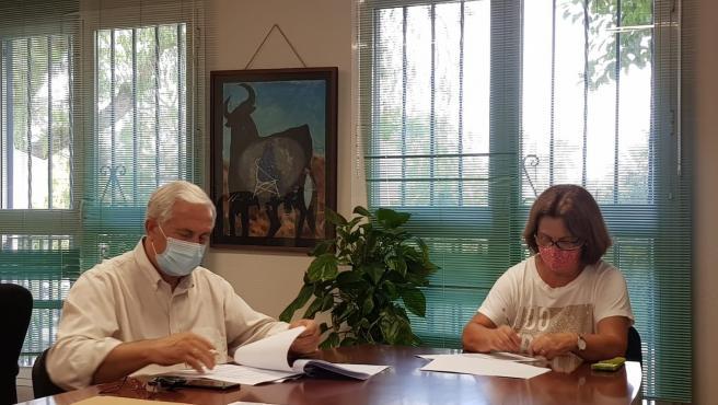 El concejal del Distrito, José del Río, y la presidenta de la asociación Serranía de Churriana, Juana Aguilar Cobos, durante la firma de un convenio