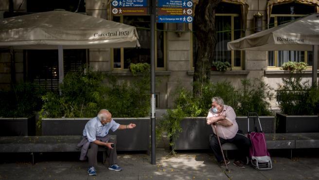 Dos hombres hablan en Barcelona manteniendo la distancia social.